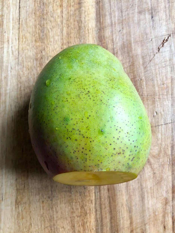 Mango on cutting board with bottom cut off