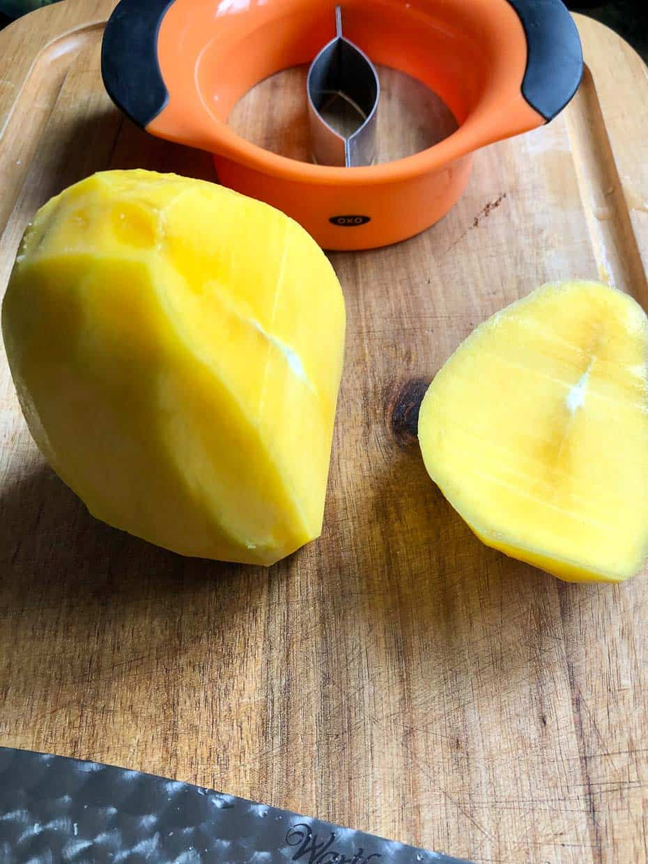 Mango being sliced from top to bottom