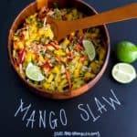 Mango slaw in wooden bowl with title written on chalkboard