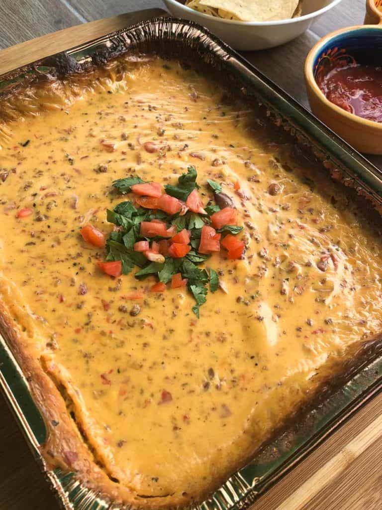 close up view of finished queso dip topped with cilantro and diced tomato