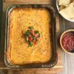 Smoked queso dip topped with cilantro and diced tomato overhead shot