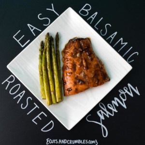 Cooked salmon with asparagus on white plate with title written on black background