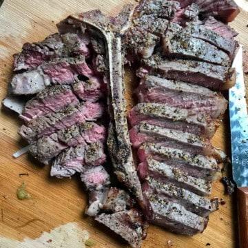 Sliced steak on cutting board overhead shot