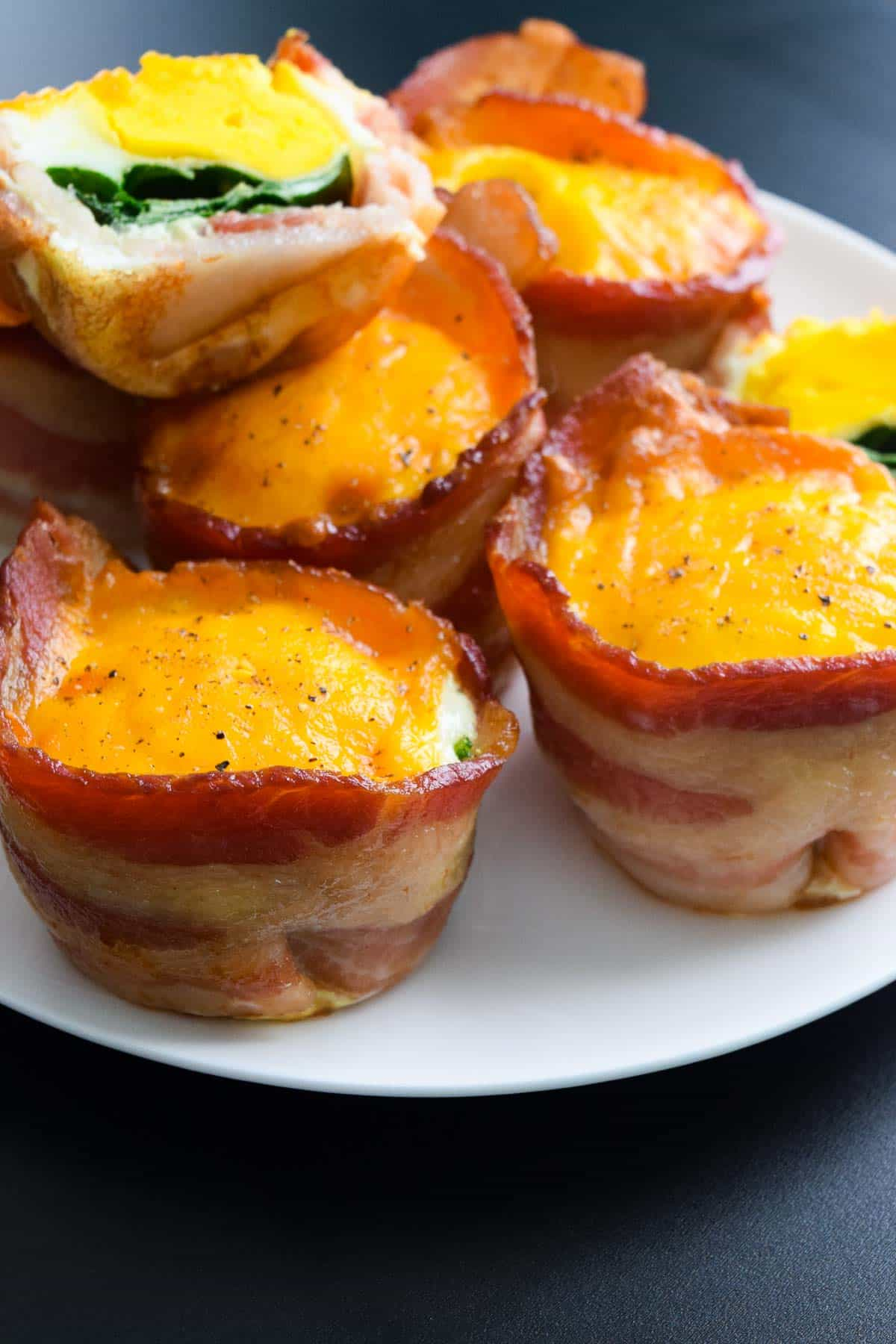 Close up view of stacked bacon egg cups on white plate
