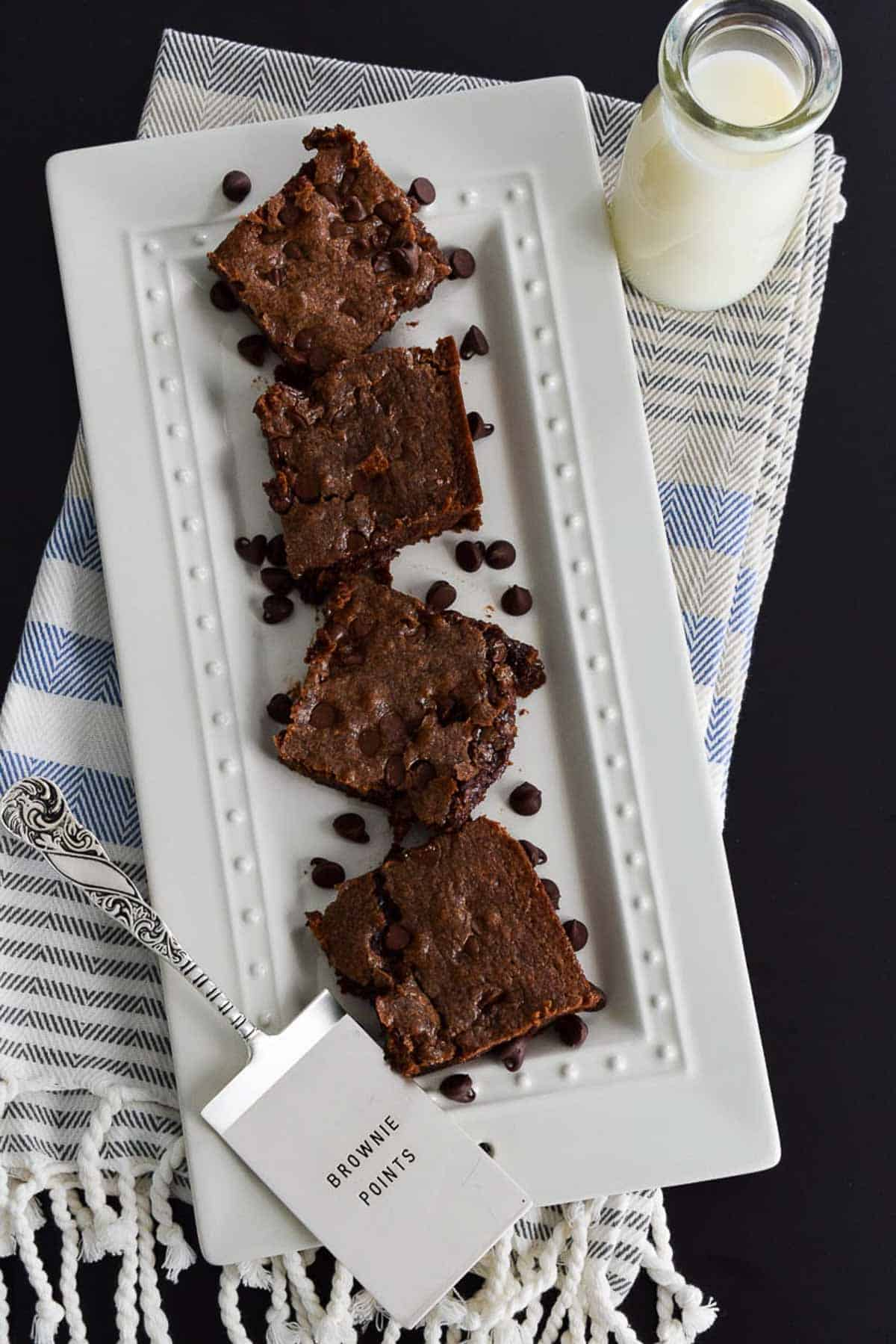Brownies on white platter on top of striped kitchen towel next to glass of milk overhead shot