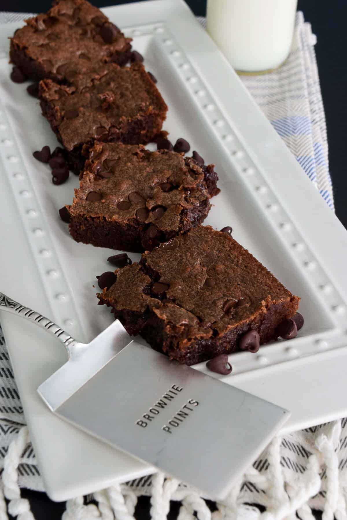 "Chocolate Chip Brownies on white platter with ""brownie points"" spatula in front"