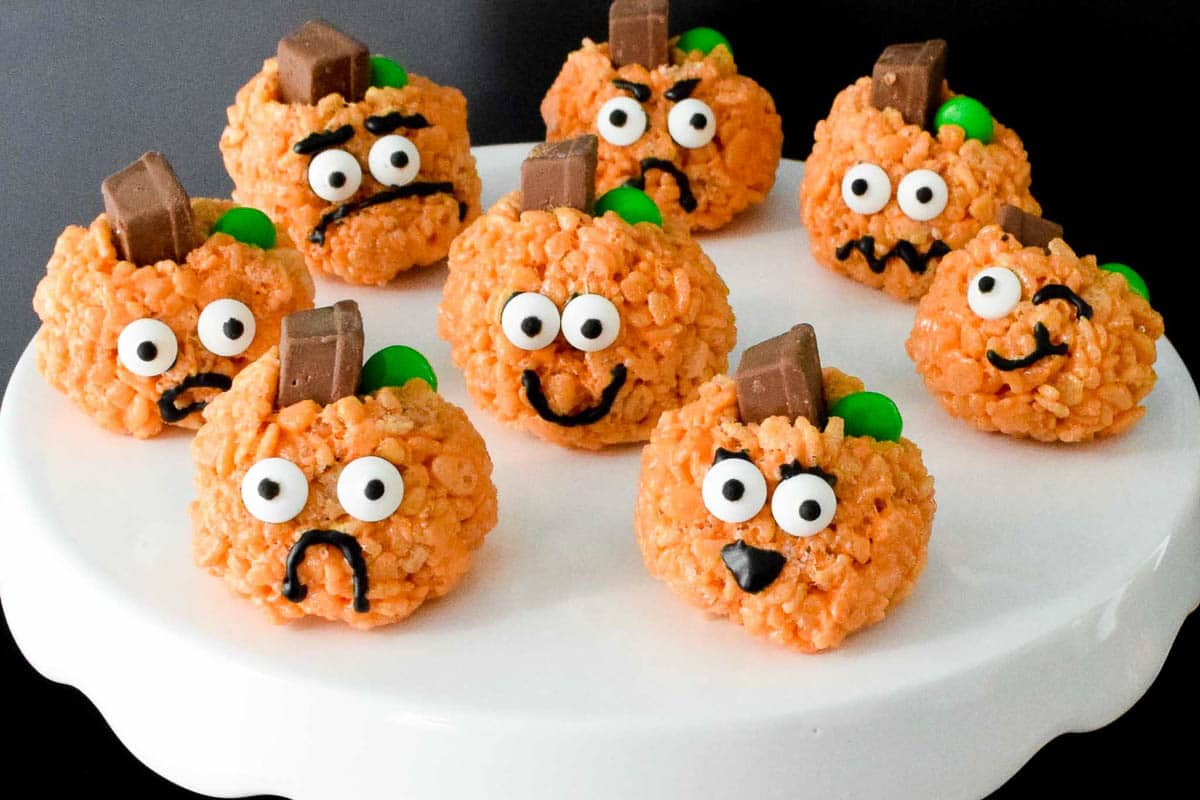 Rice Krispie Treats Pumpkins with all different faces on white cake platter up close view