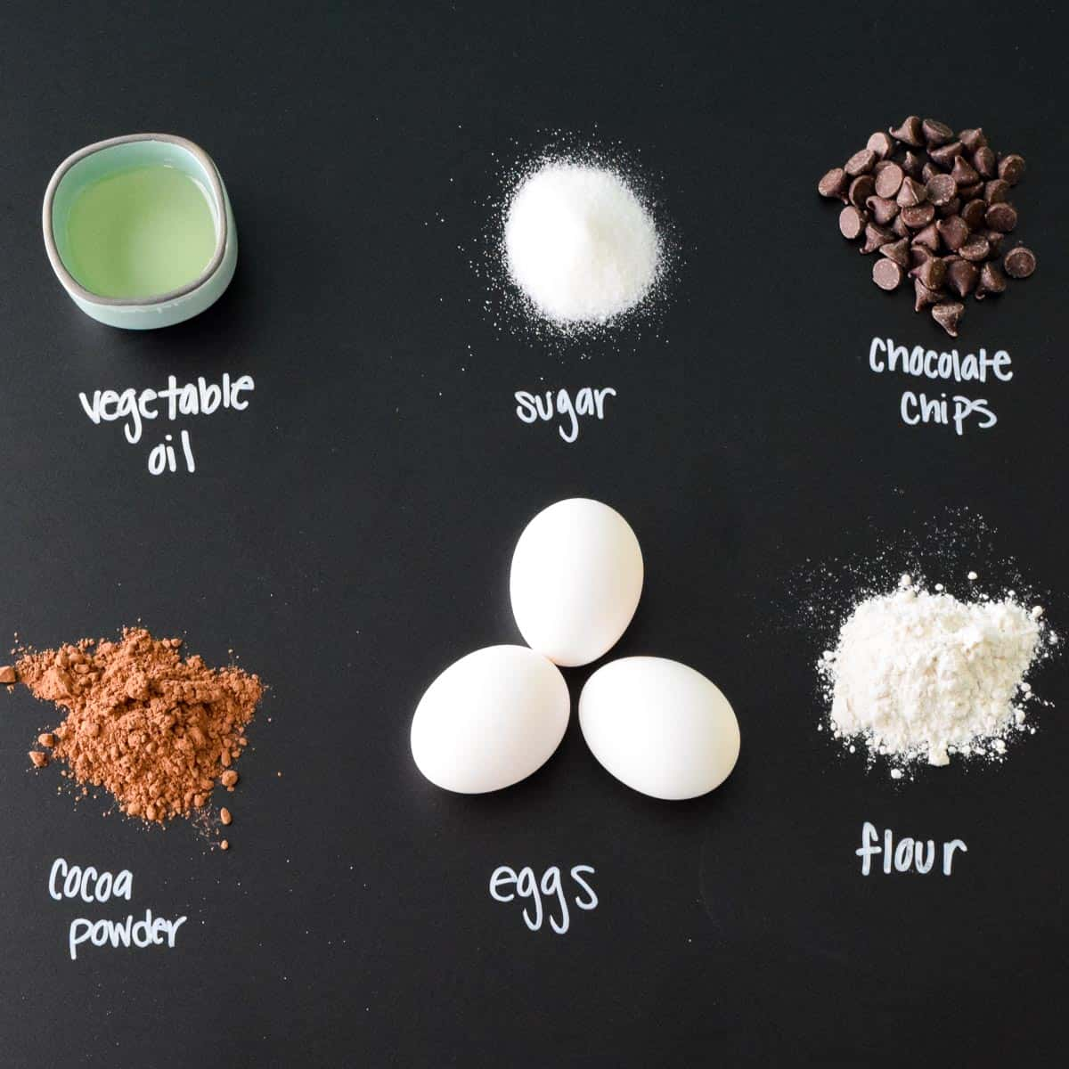 Ingredients with labels on black chalkboard overhead shot