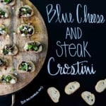 Blue Cheese and Steak Crostini on wooden platter with title written on chalkboard
