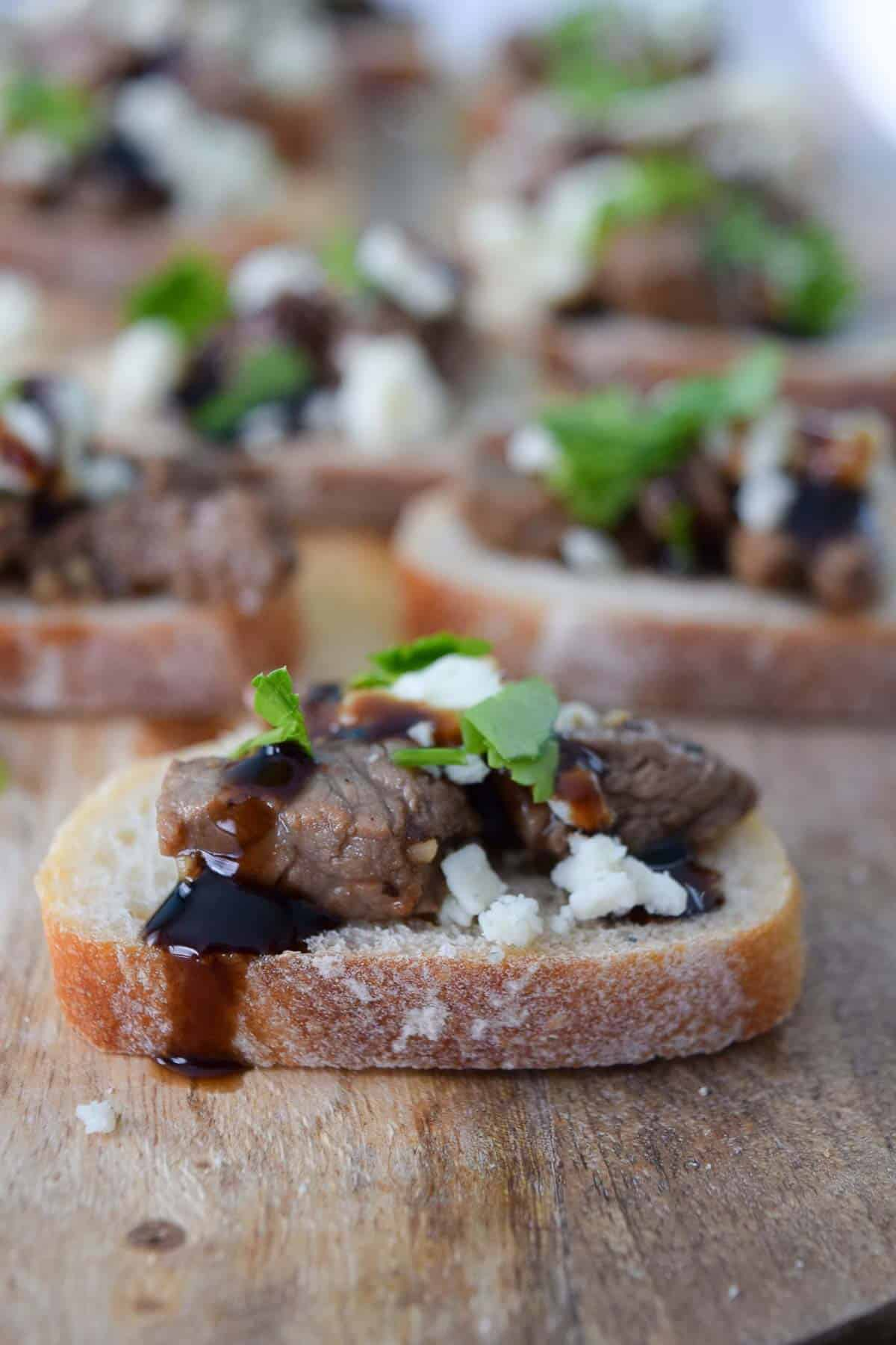 Blue Cheese and Steak Crostini topped with parsley close up side view